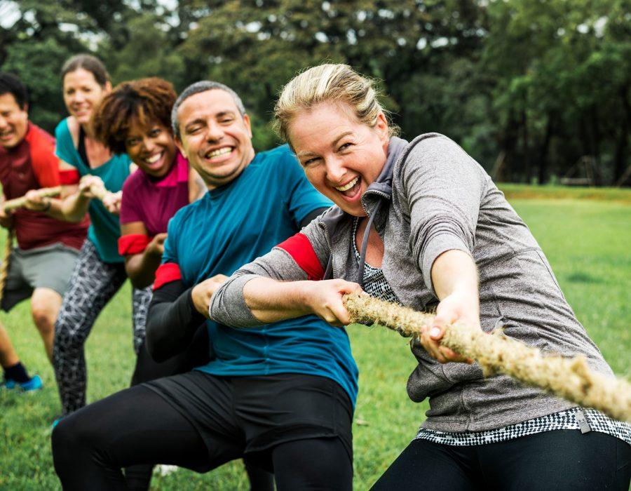 Fünf Menschen an einem Ende eines Seils - sie spielen Tauziehen.